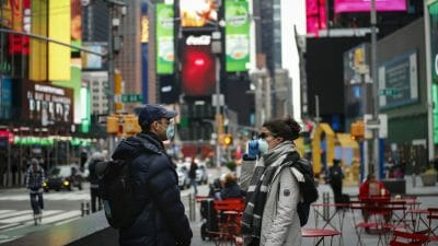 two people with masks in Times Square