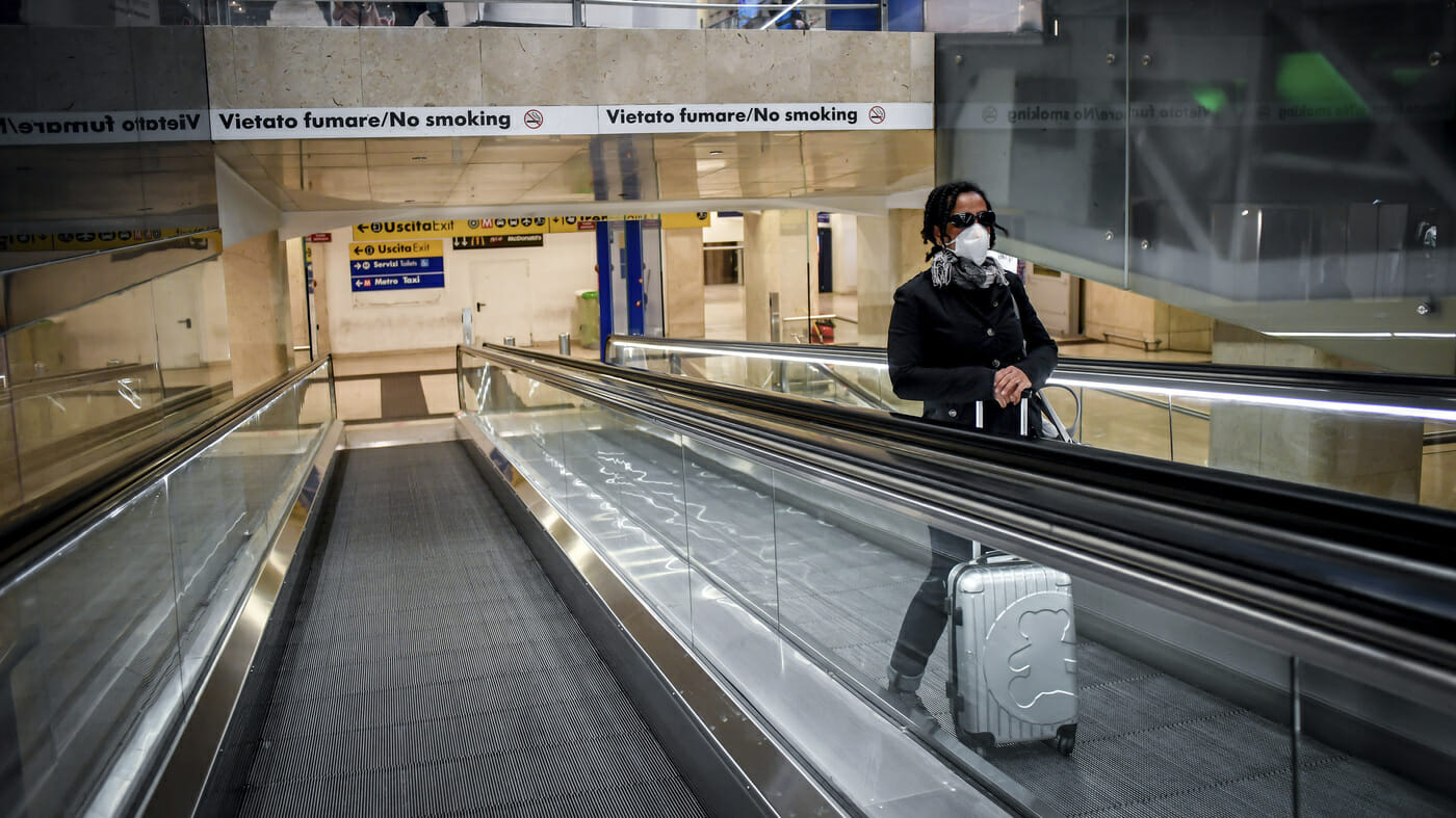 A woman wearing a medical mask rides an escalator at Milan Central train station on Sunday after Italy's governmentrestricted much of the country in an effort to stanch the spread of the coronavirus.